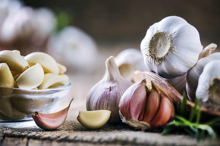 Garlic Cloves On Rustic Table. Garlic In Wooden Bowl. Fresh Peel